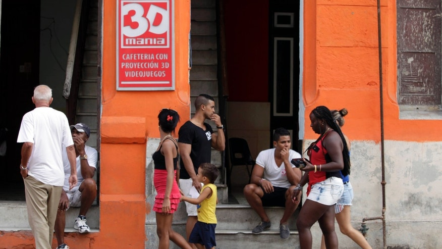 "In this Oct. 28, 2013 photo, pedestrians walk past the entrance of a private movie theater called ""3D Mania"" in Havana, Cuba. An op-ed in the Communist Party's principal newspaper acknowledges that recent decisions to outlaw the sale of imported clothing and private, home-based 3D cinemas have been widely criticized by the people and suggests that the decisions could be reconsidered. (AP Photo/Franklin Reyes)"