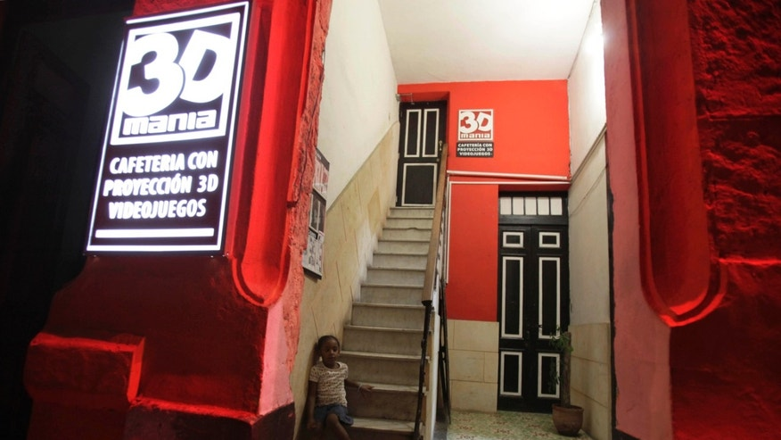 "In this Oct. 29, 2013 photo, a girl sits at the entrance of a private movie theater called ""3D Mania"" in Havana, Cuba. An op-ed in the Communist Party's principal newspaper acknowledges that recent decisions to outlaw the sale of imported clothing and private, home-based 3D cinemas have been widely criticized by the people and suggests that the decisions could be reconsidered. (AP Photo/Franklin Reyes)"