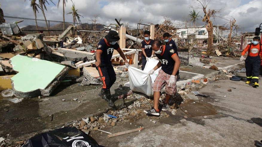 Filipino workers collect dead bodies in typhoon-hit Tacloban city, Leyte province, central Philippines on Wednesday, Nov. 13, 2013. Typhoon Haiyan, one of the strongest storms on record, slammed into six central Philippine islands on Friday leaving a wide swath of destruction. (AP Photo/Aaron Favila)
