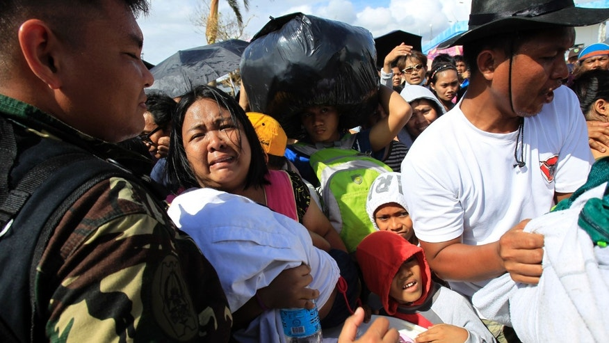A woman and her child plead from the frantic crowd to be prioritized on an evacuation flight  in Tacloban, central Philippines, Thursday, Nov. 14, 2013. Typhoon Haiyan, one of the most powerful storms on record, hit the country's eastern seaboard on Friday, destroying tens of thousands of buildings and displacing hundreds of thousands of people.  (AP Photo/Wally Santana)