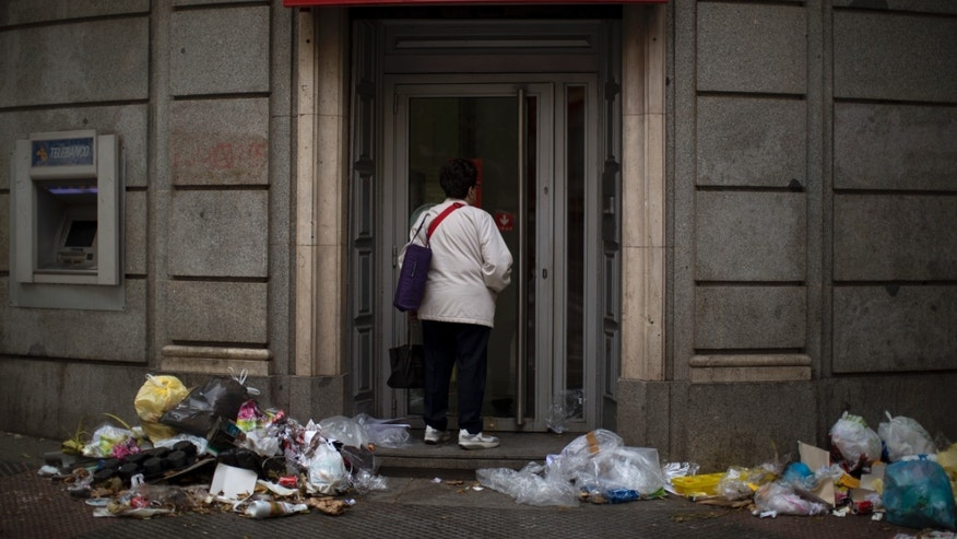 A woman enters in a bank as rubbish accumulate in the street during the ninth day of a garbage collectors strike, in Madrid, Spain, Wednesday, Nov. 13, 2013. Street cleaners and garbage collectors who work in the city's public parks walked off the job in a strike called by trade unions to contest the planned layoff of more than 1,000 workers. Madrid's municipal cleaning companies, which have service supply contracts with the city authorities, employ some 6,000 staff. (AP Photo/Emilio Morenatti)