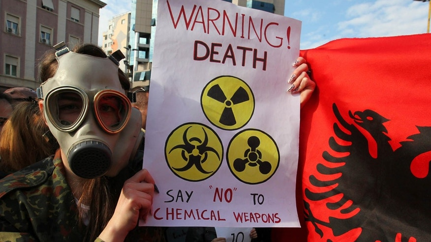 An Albanian student wears a gas mask and holds a sign  during a protest against chemical weapons during a  protest against the dismantling of Syrian chemical weapons in Albania in front of the Prime Minister's office in Tirana  Thursday Nov. 14, 2013.  Albania, a member of NATO,  has said it is studying a request by the United States to host facilities for destroying Syria's chemical weapons, but has not yet taken a decision.  (AP Photo/Hektor Pustina)