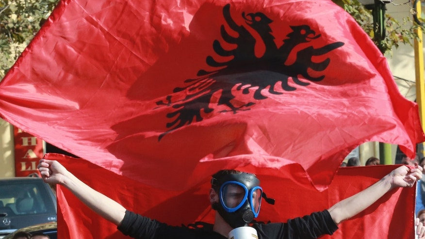 A demonstrator wearing a gas mask waves an Albanian flag during a  protest against the dismantling of Syrian chemical weapons in Albania in front of the Prime Minister's office in Tirana  Thursday Nov. 14, 2013.  Albania, a member of NATO,  has said it is studying a request by the United States to host facilities for destroying Syria's chemical weapons, but has not yet taken a decision.  (AP Photo/Hektor Pustina)