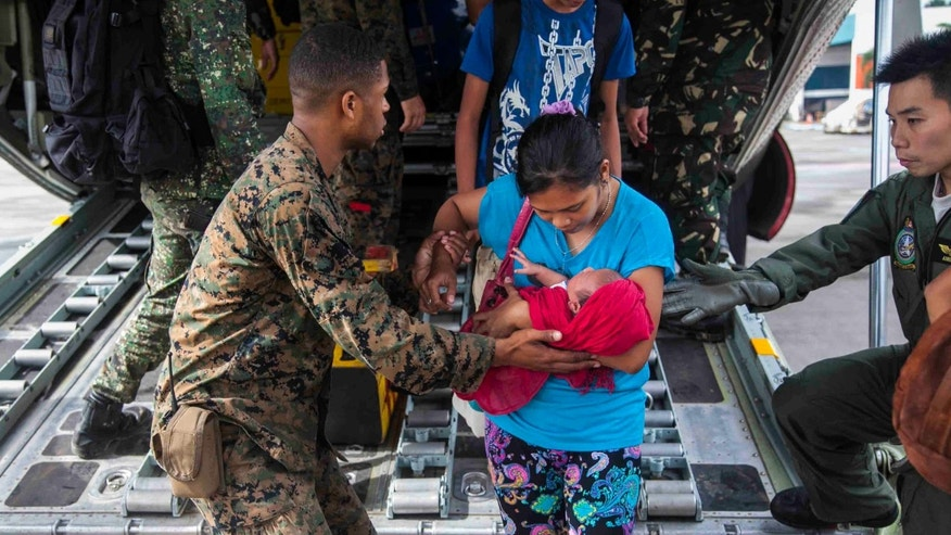 U.S. Marine Lance Cpl. Xavier L. Cannon and members of the Philippine Armed Forces help civilians displaced by Typhoon Haiyan disembark a C-130 aircraft Tuesday, Nov. 12, 2013 at Villamor Air Base. U.S. service members are assisting the Armed Forces of the Philippines as they preform recovery efforts for the people affected in the aftermath of Typhoon Haiyan. The number of American troops helping the relief effort in the typhoon-hit Philippines could triple to more than 1,000 by the end of the week, U.S. officials said Wednesday.  (AP Photo/U.S. Marine Corps, Lance Cpl. Anne K. Henry)