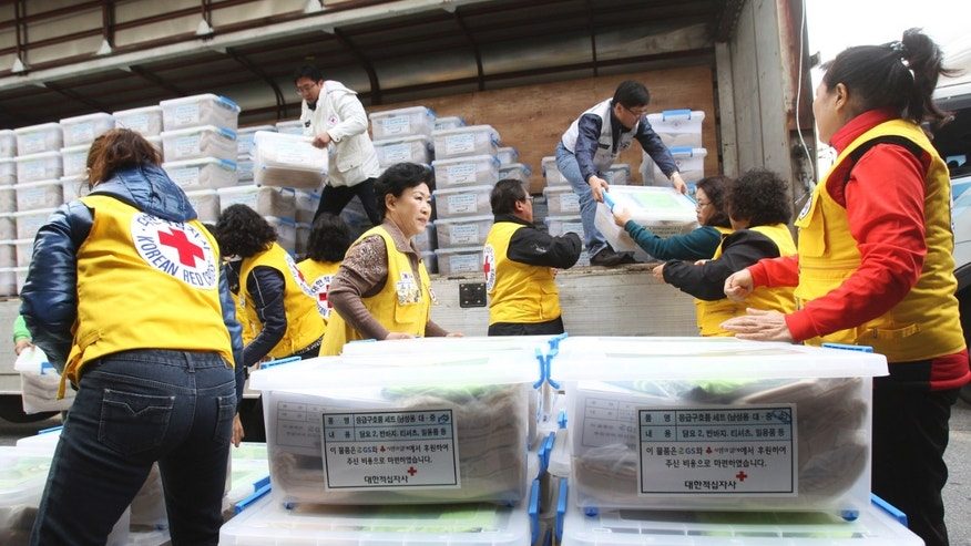Members of South Korean Red Cross unload emergency relief packages from a truck at Incheon Airport Cargo Terminal in Incheon, South Korea, Thursday, Nov. 14, 2013. The Red Cross plans to send US$1 million and 10,000 sets of relief packages for the Typhoon Haiyan victims in the Philippines. (AP Photo/Ahn Young-joon)