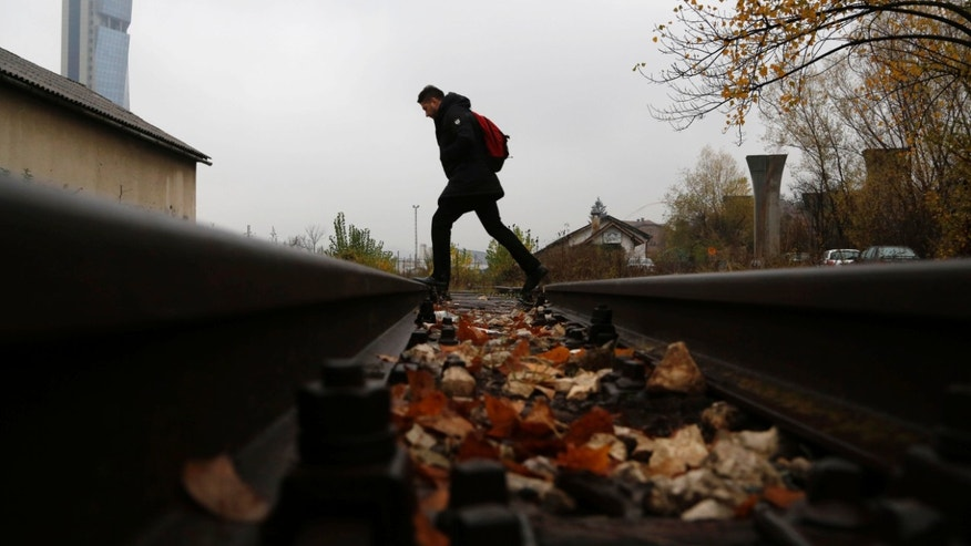 In this photo taken on Friday, Nov. 8, 2013 a Bosnian man  walks over rails Bosnian town of Sarajevo. They were seen as a shining example of Bosnia's rebirth from war: a fleet of high-speed trains built-to-order in the West. Eight years later, they haven't made a single ride. The reason: They're just too fast for Bosnia's 60-year-old rails.  (AP Photo/Amel Emric)