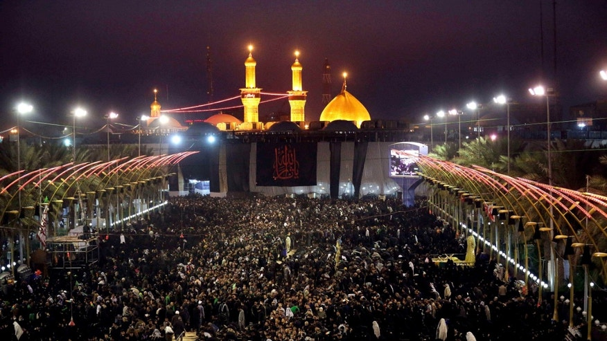 Shiite faithful worshippers gather between the holy shrines of Imam Abbas and Imam Hussein, seen in the background, during Muharram, an important period of mourning for Shiites in the Shiite holy city of Karbala, 50 miles (80 kilometers) south of Baghdad, Iraq, Wednesday, Nov. 13, 2013. The remembrance of Muharram marks the anniversary of the Battle of Karbala when Imam Hussein, a grandson of Prophet Muhammad, was killed. (AP Photo/Hadi Mizban)