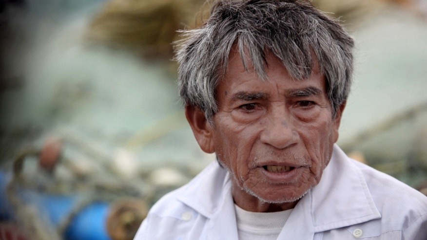 In this Nov. 9, 2013 photo, fisherman Raul Hurtado, 64, speaks during an interviewoutside of his small shack where he sells seafood in the port city of Veracruz, Mexico. Hurtado is a local legend, the man who found and lost millions of dollars' worth of Aztec gold almost four decades ago, was tossed in prison, then found peace making $150 a month selling octopus and other seafood from a thatched-roof shack. (AP Photo/Felix Marquez)