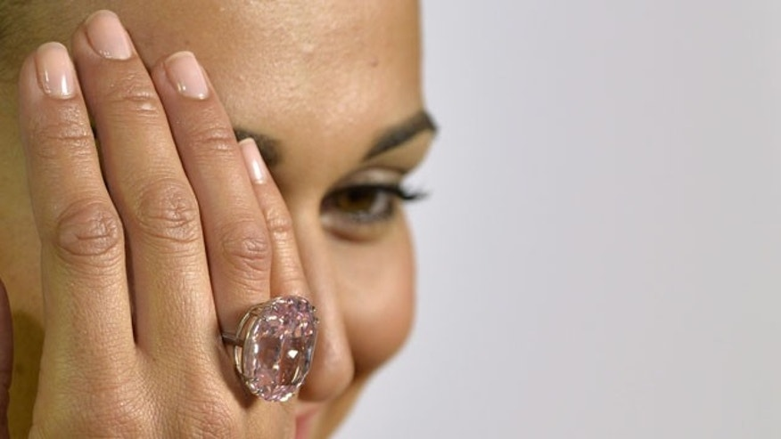 "FILE - A Wednesday, Sept. 25, 2013 photo from files showing an unidentified Sotheby's employee displaying ""The Pink Star"" diamond weighing 59.6 carat, during a preview at Sotheby's, in Geneva, Switzerland. (AP Photo)"