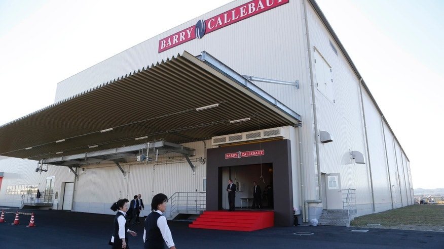 Japanese employees of Zurich, Switzerland-based cocoa and chocolates maker Barry Callebaut walk by its factory which officially opened in Takasaki, Gunma Prefecture, Japan Thursday, Nov. 14, 2013. Given the trouble Japan has in persuading its own companies to invest at home, the opening of the chocolate factory in this railway hub northwest of Tokyo is a rare milestone in Prime Minister Shinzo Abe's crusade to lure more foreign investment. (AP Photo/Koji Sasahara)