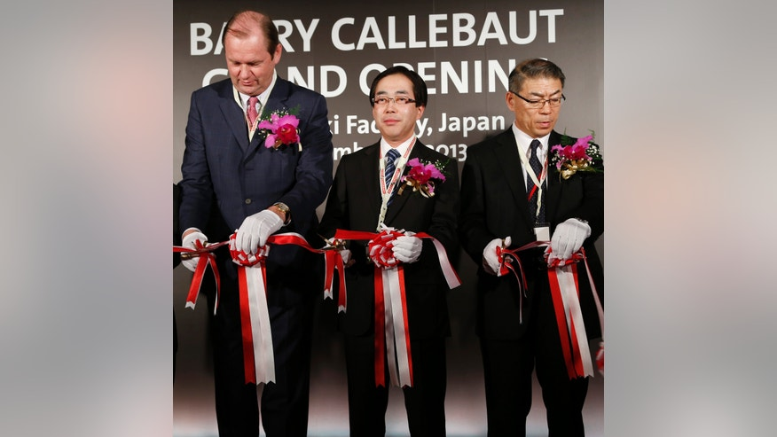 Barry Callebaut AG Chief Executive Officer Juergen Steinemann, left, Gunma Prefecture Vice Gov. Hiromi Yoshikawa, center, and Barry Callebaut Japan Managing Director Fumitaka Nakano cut the tape during an official opening ceremony of a factory of the Zurich, Switzerland-based cocoa and chocolate maker in Takasaki, Gunma Prefecture, Japan Thursday, Nov. 14, 2013. Given the trouble Japan has in persuading its own companies to invest at home, the opening of the chocolate factory in this railway hub northwest of Tokyo is a rare milestone in Prime Minister Shinzo Abe's crusade to lure more foreign investment.  (AP Photo/Koji Sasahara)