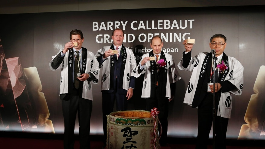 Barry Callebaut Japan Managing Director Fumitaka Nakano, right, toasts with Malaysia-based Barry Callebaut's Chocolate in the Asia-Pacific President Mikael Neglen, left, Barry Callebaut Chief Executive Officer Juergen Steinemann, second left, and Belgian Ambassador to Japan Luc Liebaut after breaking a Japanese sake barrel for celebration during an official opening ceremony of a factory of the Zurich, Switzerland-based cocoa and chocolate maker in Takasaki, Gunma Prefecture, Japan, Thursday, Nov. 14, 2013. Given the trouble Japan has in persuading its own companies to invest at home, the opening of the chocolate factory in this railway hub northwest of Tokyo is a rare milestone in Prime Minister Shinzo Abe's crusade to lure more foreign investment. (AP Photo/Koji Sasahara)