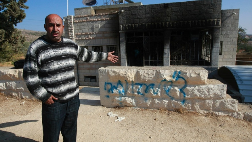 "A Palestinians man shows a damaged house with spray-painted the graffiti in Hebrew reading, ""Greetings from Eden. Revenge."" in the village of Sinjil near the West Bank City of Ramallah, Thursday, Nov. 14, 2013. Israeli police said vandals have set fire to a Palestinian home in the West Bank and scrawled graffiti on it. Police spokesman said the incident appeared to have come in response to the killing of an Israeli soldier, Eden Attias, on Wednesday by a Palestinian teenager. (AP Photo/Majdi Mohammed)"