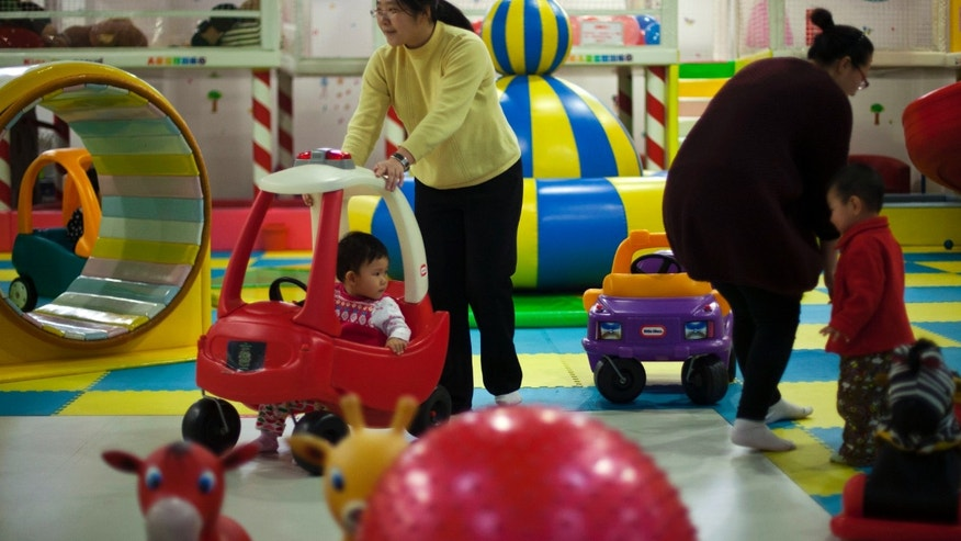 Jan. 10, 2013 - FILE photo of parents playing with their children at a shopping mall in Beijing.  China will loosen its decades-old one-child policy and abolish a much-criticized labor camp system, its ruling Communist Party said.  Friday,