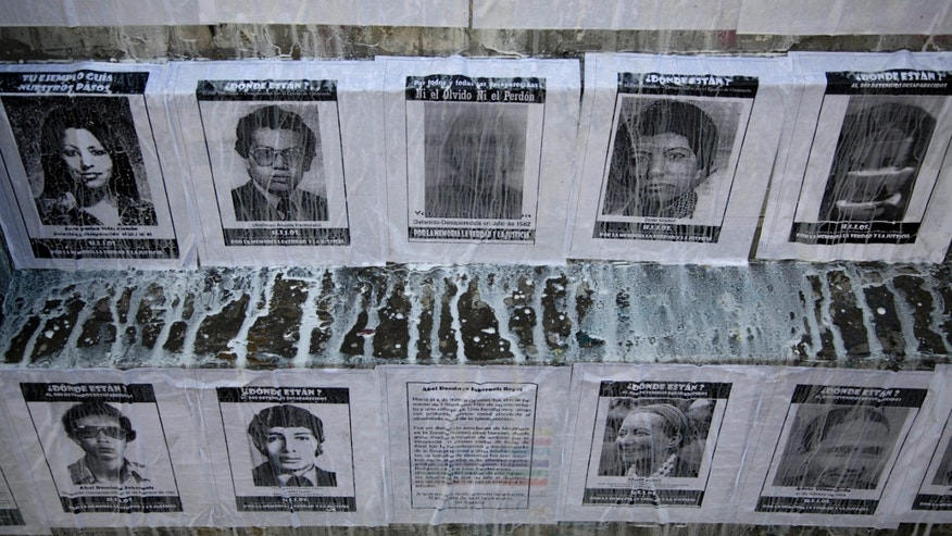 In this Nov. 9, 2013 photo, portraits of people who disappeared during the civil war cover a wall outside Congress in Guatemala City. A handful of Guatemalans have launched tiny, homegrown attempts to draw attention to what human rights groups and the Inter-American Court of Human Rights call a deplorable lack of official action in the face of one of the worst unresolved cases of human-rights violations in the 20th century. (AP Photo Moises Castillo)