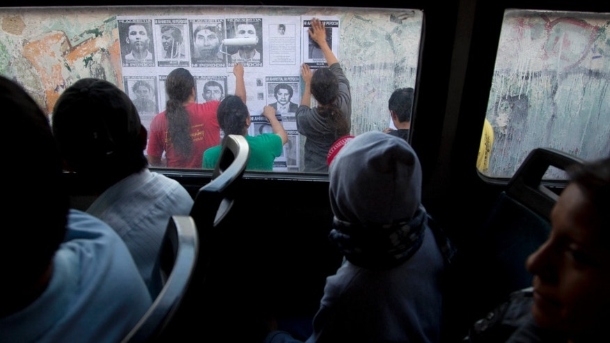 In this Nov. 9, 2013 photo, bus passengers watch others paste the portraits of people who disappeared during the civil war on a wall in downtown Guatemala City.  Almost all the victims are believed to have been killed, often after being raped, tortured, or both, then buried in mass graves, ditches and wells. Many were hurled from helicopters into the sea or volcanic craters. (AP Photo Moises Castillo)