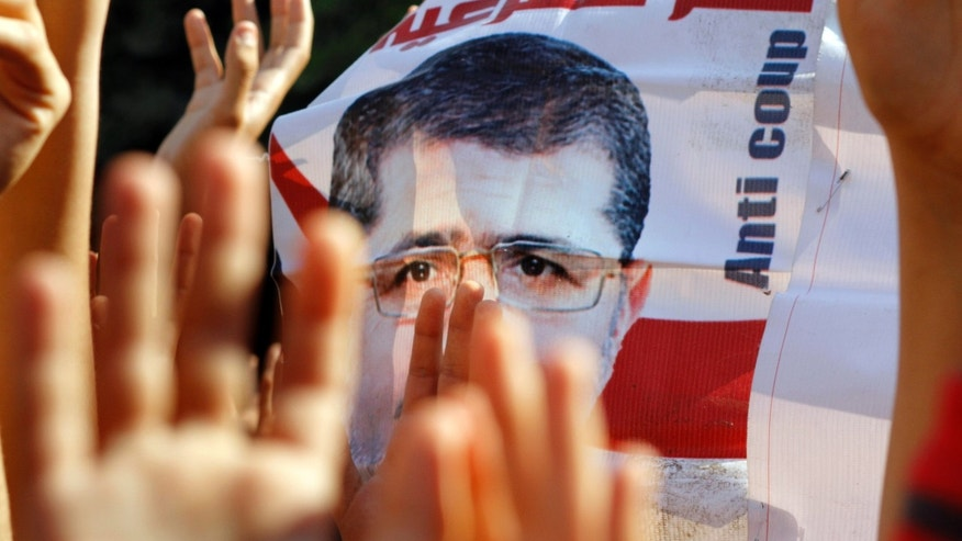 "Supporters of Egypt's ousted President Mohammed Morsi raise his poster and their hands with four raised fingers, which has become a symbol of the Rabaah al-Adawiya mosque, where Morsi supporters had held a sit-in for weeks that was violently dispersed in August, during a protest in Cairo, Egypt, Friday, Nov. 15, 2013. The Arabic on the posters reads, ""yes to legitimacy."" Authorities moved Egypt's ousted president from a hospital room to solitary confinement in a massive prison complex Thursday, a security official said, as his son claimed officials denied a family visitation request after lawyers delivered a message from the leader.(AP Photo/Amr Nabil)"