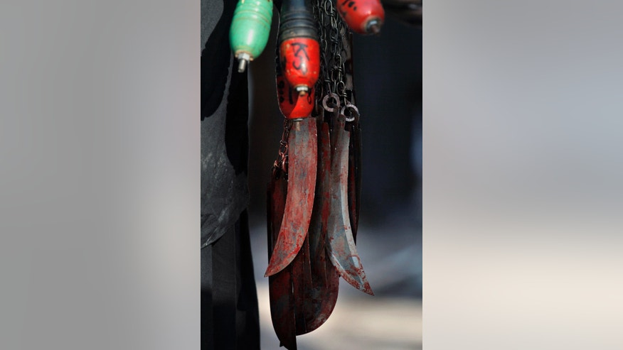 A Pakistani Shiite Muslim carries blood-stained knives attached to chains after flagellating himself during an Ashoura procession in Rawalpindi, Pakistan, Friday, Nov. 15, 2013. Ashoura commemorates the martyrdom of Imam Hussein, the grandson of Prophet Muhammad at the Battle of Karbala, Iraq, in the year 680 A.D. (AP Photo/Anjum Naveed)