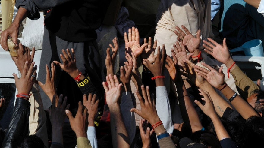Pakistani Shiite Muslims raise their hands to get free food distributed by a businessman during an Ashoura procession in Rawalpindi, Pakistan, Friday, Nov. 15, 2013. Ashoura commemorates the martyrdom of Imam Hussein, the grandson of Prophet Muhammad at the Battle of Karbala, Iraq, in the year 680 A.D. (AP Photo/Anjum Naveed)
