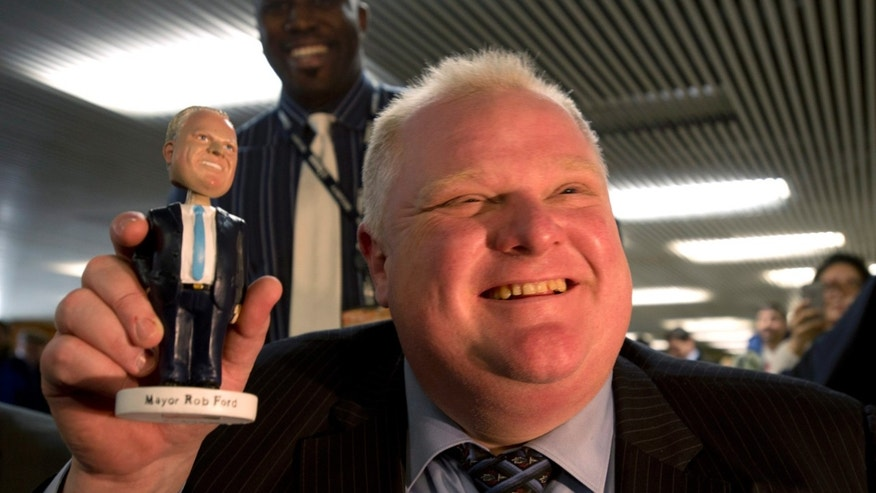 FILE - In this Tuesday, Nov. 12, 2013 file photo, Toronto Mayor Rob Ford holds a bobblehead doll depicting him at Toronto City Hall. An electoral map of the 2010 mayoral election shows that Ford's voter base resides mainly in a more conservative constituency than the downtown electorate. (AP Photo/The Canadian Press, Frank Gunn)