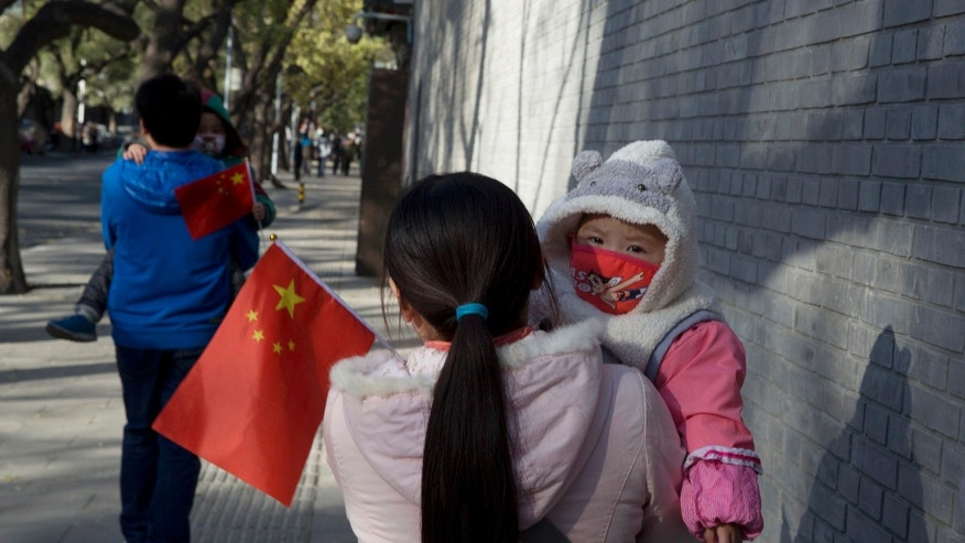 Visitors to the forbidden city carry children holding the Chinese national flags in Beijing, China, Saturday, Nov. 16, 2013. Some 15 million to 20 million Chinese parents will be allowed to have a second baby after the Chinese government announced Friday, Nov. 15, 2013 that couples where one partner has no siblings can have two children, in the first significant easing of the country's strict one-child policy in nearly three decades.(AP Photo/Ng Han Guan)
