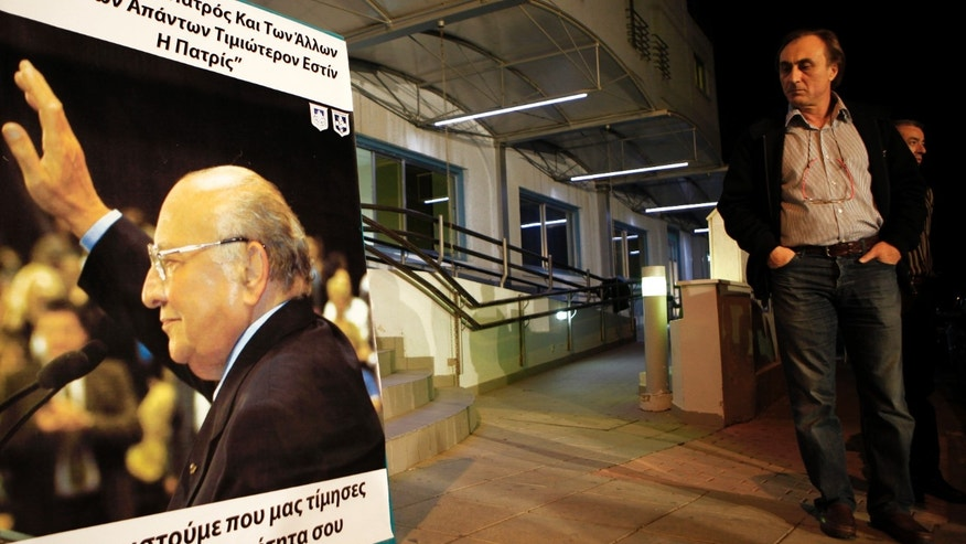 A man looks at a poster showing the former Cyprus President Glafcos Clerides outside of the clinic in capital Nicosia, Cyprus, Friday, Nov. 15, 2013. Former Cyprus President Glafcos Clerides, who dedicated most of his 50 years in politics to trying to reunify the ethnically split island and guided it to European Union membership, has died. He was 94.(AP Photo/Petros Karadjias)