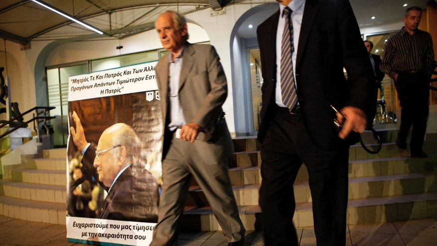 Joseph Kasios, Clerides' personal physician, left, exits the clinic to speak to the media as he passes by a poster showing the Former Cyprus President Glafcos Clerides, in capital Nicosia, Cyprus, Friday, Nov. 15, 2013. Former Cyprus President Glafcos Clerides, who dedicated most of his 50 years in politics to trying to reunify the ethnically split island and guided it to European Union membership, has died. He was 94. (AP Photo/Maria Karadjias)