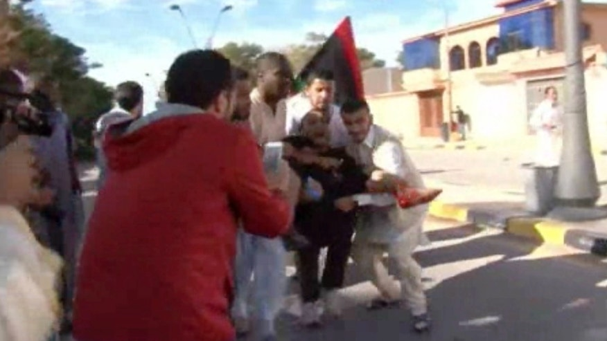 This image made from video shows an injured protester being carried away from the scene in Tripoli, Libya after militiamen attacked peaceful protesters demanding the disbanding of the country's rampant armed groups on Friday, Nov. 15, 2013, killing tens of people as they opened fire on the march with heavy machine guns and rocket-propelled grenades. (AP Photo via AP video)