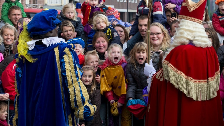 "Children scream as they interact with  ""Zwarte Piet"" or ""Black Pete"", left, and Sinterklaas, or Saint Nicholas, after they arrived by steamboat in Hoorn, north-western Netherlands, Saturday Nov. 16, 2013. The tradition of Sinterklaas, the Dutch version of Santa Claus, is the subject of debate, where opponents say Black Petes are an offensive caricature of black people while supporters say Pete is a figure of fun whose appearance is harmless, his face soot-stained from going down chimneys to deliver present for the children. (AP Photo/Peter Dejong)"