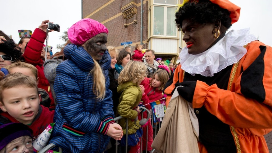 "Nov. 16, 2013: Children, some with faces painted black, wait  for  ""Zwarte Piet"" or ""Black Pete"", right, to hand them candy after they arrived with Sinterklaas, or Saint Nicholas, in Hoorn, north-western Netherlands."