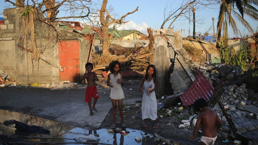 Survivors of Typhoon Haiyan stand along the debri strewn streets, Saturday, Nov. 16, 2013 in Tacloban city, Leyte province, central Philippines. Typhoon Haiyan, one of the most powerful storms on record, hit the country's eastern seaboard Nov. 8, leaving a wide swath of destruction. (AP Photo/Wong Maye-E)