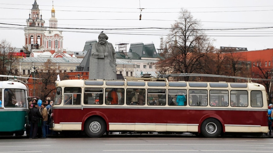 Visitors go inside old trolleybuses standing at the square near the Kremlin, with a monument to Karl Marx in the background,  in Moscow, Russia, Saturday, Nov. 16, 2013. Pieces of the Soviet past were crawling down some of Moscow's main streets as the city transportation system marked the 80th anniversary of the trolleybus system with a procession of vintage vehicles. The trolleybus system doesn't have the cachet of Moscow's art-festooned subway, but the cortege of buses dating back to the 1950s attracted a small throng when it stopped at the square outside the Bolshoi Theater on Saturday. (AP Photo/Pavel Golovkin)