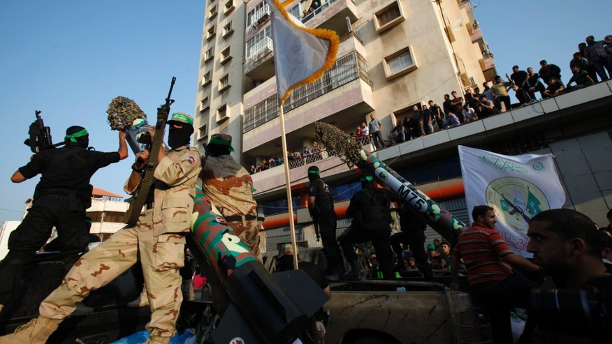 Masked Palestinian members of the Ezz Al-Din Al Qassam brigade, the military wing of Hamas, stand behind mock rockets on trucks during a parade to mark the anniversary of a battle against Israel in Gaza City.