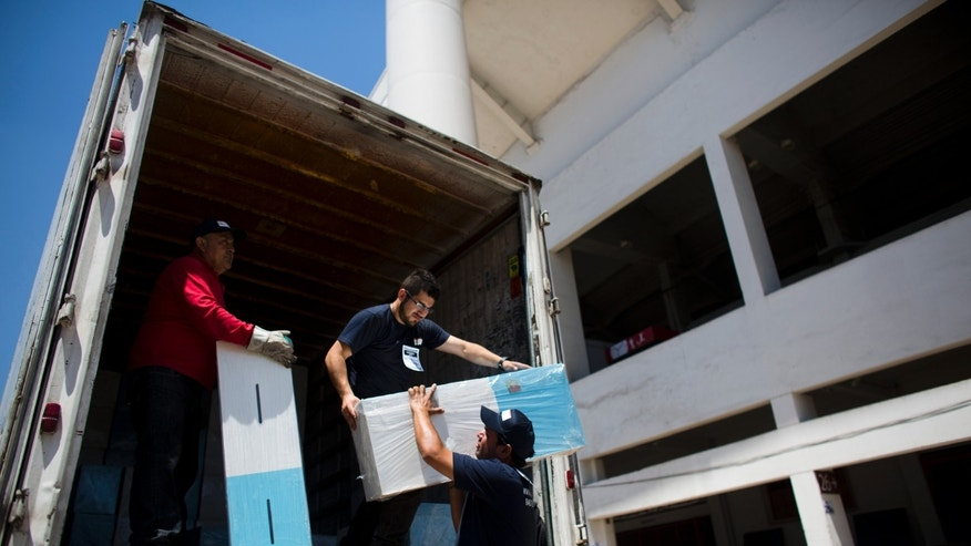 Workers unload ballot boxes at the National Stadium in Santiago, Chile, Friday, Nov. 15, 2013. Chile will hold general elections on Nov. 17. (AP Photo/Victor R. Caivano)