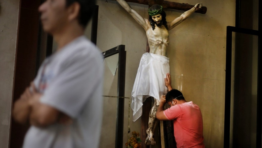 A Filipino man prays on a statue of Jesus Christ prior to a Mass at Santo Nino church, which was damaged by Typhoon Haiyan in Tacloban, Philippines, Sunday, Nov. 17, 2013. Typhoon Haiyan, one of the most powerful storms on record, hit the country's eastern seaboard Nov. 8, leaving a wide swath of destruction.   (AP Photo/Dita Alangkara)