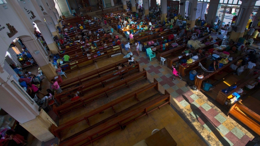 Typhoon Haiyan survivors enter a Catholic cathedral, where crowds of homeless people are squatting in Tacloban, Philippines, before church mass on Sunday Nov. 17, 2013. Typhoon Haiyan, one of the most powerful storms on record, hit the country's eastern seaboard Nov. 8, leaving a wide swath of destruction. (AP Photo/David Guttenfelder)