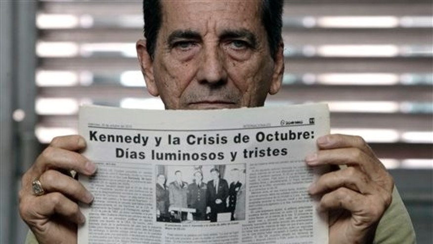 "In this Oct. 25, 2013 photo, Manuel Rodriguez, 73, holds an article published by the Granma newspaper in 2010 about U.S. President John F. Kennedy in Havana, Cuba. The newspaper reads in Spanish, ""Kennedy and the October crisis: Shining and sad days."" In October 1962, Rodriguez was a member of the military reserve when he was sent to the municipality of Cotorro to help defend Cuba against a possible U.S. invasion, during the Cuban Missile Crisis and one year after the Bay of Pigs invasion. (AP Photo/Franklin Reyes)"