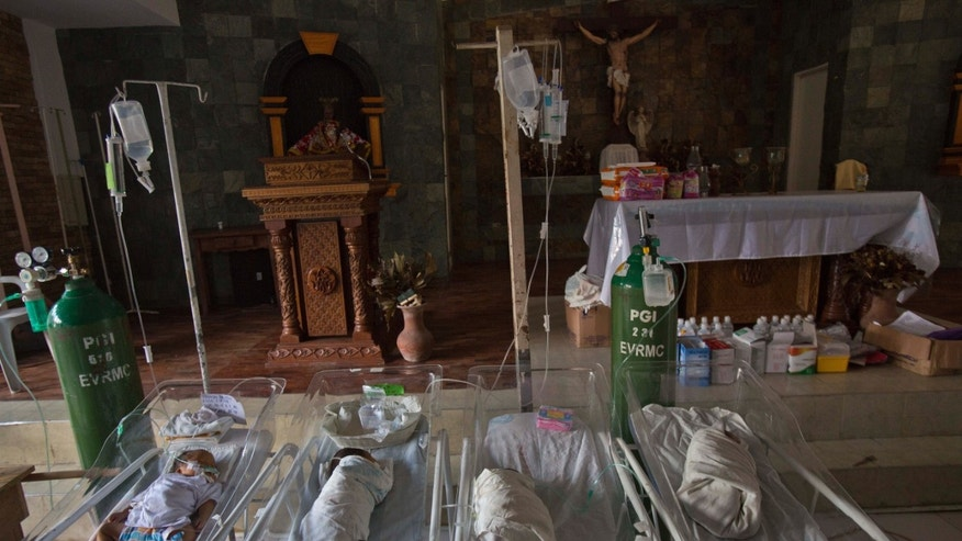 Sick and premature babies lie in cribs on the alter of a Catholic chapel inside the Eastern Visayas Regional Medical Center in Tacloban on Saturday Nov. 16, 2013. The chapel is now being used to care for infants after Typhoon Haiyan destroyed the original facility of the hospital. (AP Photo/David Guttenfelder)