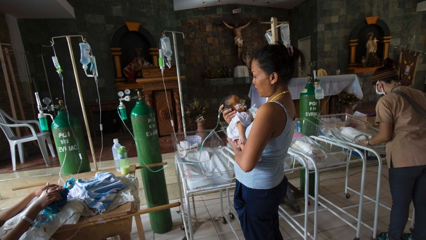 Nanette Salutan holds her baby son Bernard in her arms in front of the altar of a Catholic chapel inside the Eastern Visayas Regional Medical Center in Tacloban, Philippines on Saturday Nov. 16, 2013. The chapel is now being used to care for infants after Typhoon Haiyan destroyed the original facility of the hospital. (AP Photo/David Guttenfelder)
