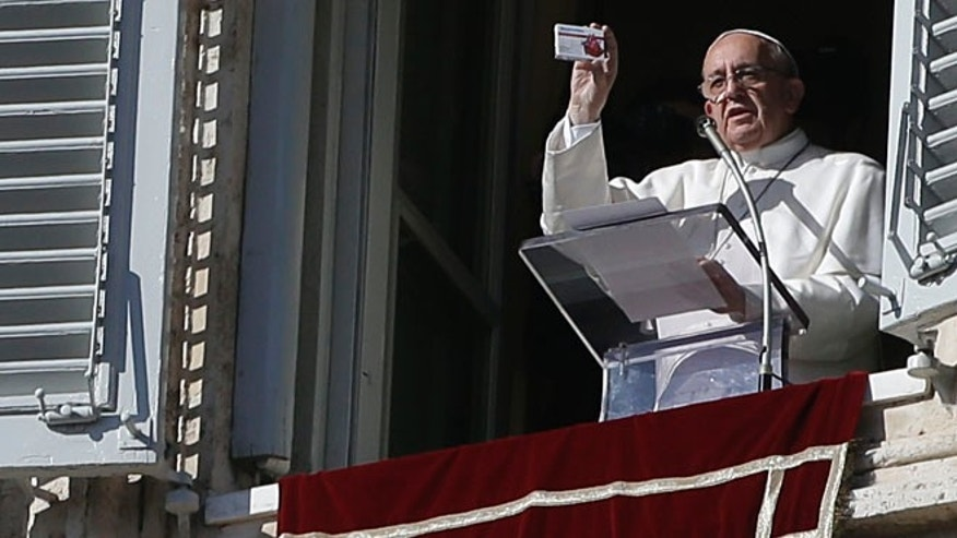 Nov. 17, 2013: Pope Francis shows a box shaped like a pill box but which contains a rosary during his traditional Sunday appearance in St. Peter's Square at the Vatican.