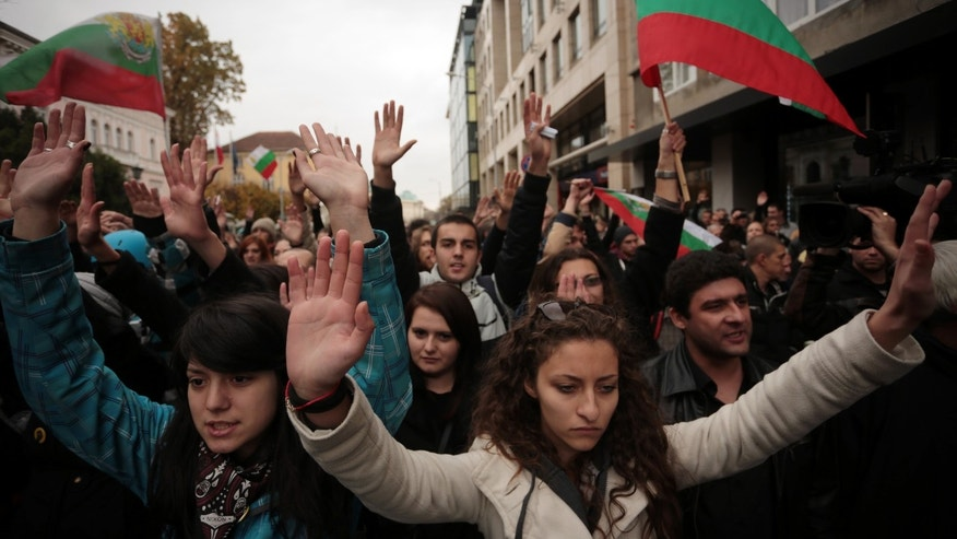 This Tuesday, Nov. 12, 2013, photo shows students raising their hands to signal they are participating in a non-violent protest, near the Bulgarian Parliament during anti-government protest in Sofia. Ivaylo Dinev believes the time has come to change his world.  To do so, he's chosen a tactic straight from the 1960s _ the sit-in. The 24-year-old anthropology student is the informal leader of a group that has occupied Sofia University's main building since the end of October in hopes of forcing Bulgaria's Socialist-led government to resign.  The Sofia University occupation has spawned other university sit-ins, energizing a 5-month-old movement against the government over allegations that its leaders have ties to shady businessmen. Public opinion polls show about two-thirds of Bulgaria's 7.3 million people support the protesters, including several hundred university professors. (AP Photo/Valentina Petrova)