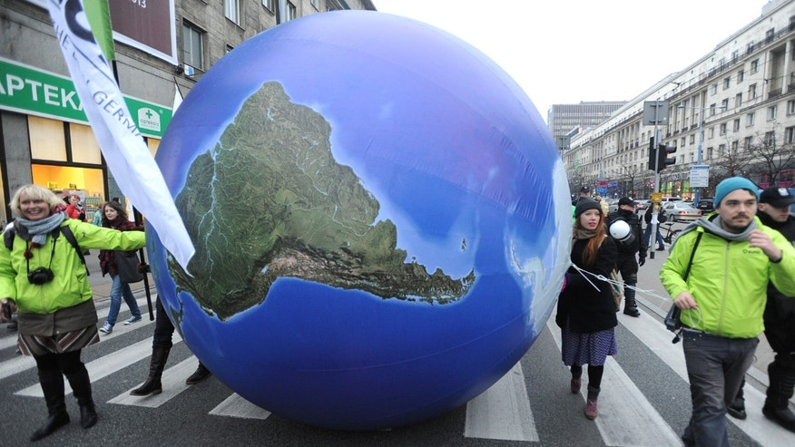 Climate activists roll a giant Globe during an environmentalist march to campaign against global warming, in downtown Warsaw, Poland, Saturday, Nov. 16, 2013. The demonstration coincides with a two-week United Nations conference that is to prepare groundwork for a new climate deal expected in 2015. (AP Photo/Alik Keplicz)