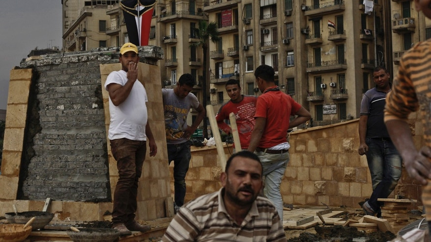 In this Sunday, Nov. 17, 2013 photo, Egyptian municipality laborers work on a memorial base two days before the commemoration of deadly clashes with security forces in 2011, in Tahrir Square, Cairo. Egypt's government wants the memorial to commemorate those killed in protests over two years of unrest in the country, but some say the memorial is just a means to make it appear there's political stability in the Arab world's most populous nation. (AP Photo/Nariman El-Mofty)