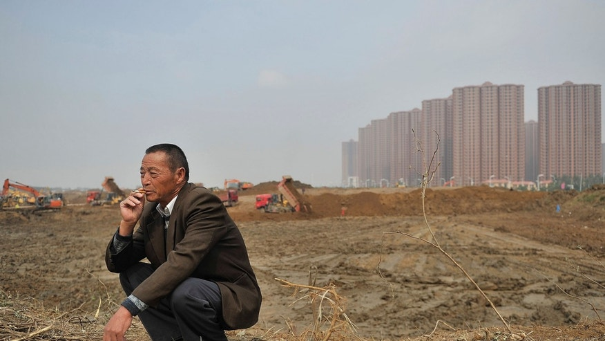 In this photo taken Oct 19, 2013, a farmer squats over what used to his land that was bought over by developers to build high-rise apartments in Hefei in eastern China's Anhui province.  The eastern Chinese region is experimenting with letting farmers mortgage or transfer control of their publicly owned land, in what could help spread prosperity to the impoverished countryside and become one of China's most pivotal rural land reforms in 35 years.(AP Photo) CHINA OUT