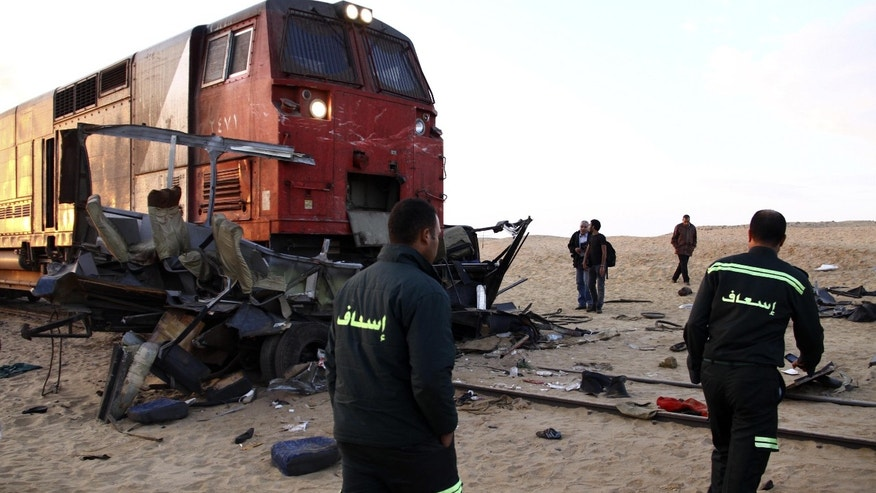 Ambulance workers inspect the wreckage of vehicles struck by a train at the site of a deadly train accident near the village of Dahshur, about 40 kilometers (25 miles) south of Cairo, Egypt, Monday, Nov. 18, 2013. A cargo train traveling south of Egypt's capital slammed into vehicles crossing the tracks early Monday, killing dozens of people, many from the same family returning from a wedding party, state TV and the head of emergency services said. (AP Photo/Ahmed Gomaa)