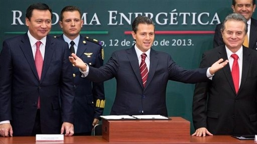 FILE - In this Aug. 12, 2013 file photo, Mexico's President Enrique Pena Nieto, center, greets the audience flanked by the Interior Secretary Miguel Angel Osorio Chong, left, and Energy Secretary Pedro Joaquin Coldwell during the ceremony to announce his proposal that would allow private firms to participate in the oil industry in Mexico City. Legislators from Mexicos two pro-energy reform political parties say they support constitutional changes to allow the government to grant licenses and share oil and profits with giants such as Exxon or Chevron. (AP Photo/Eduardo Verdugo, File)