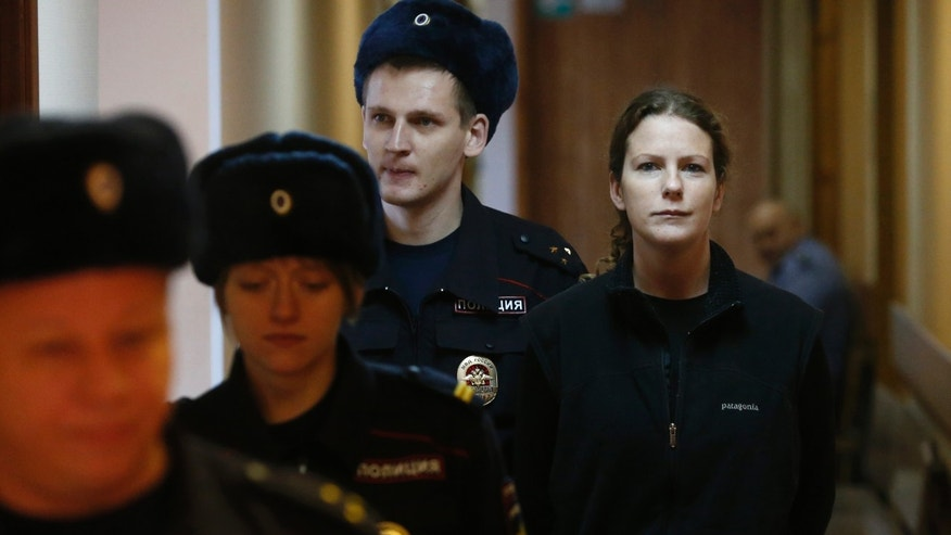Greenpeace International activist Ana Paula Alminhana Maciel of Brazil, right, is escorted to a court room for hearing that considers investigators request to extend the detention of 30 members of the Arctic Sunrise Greenpeace International ship in St.Petersburg, Russia, Monday, Nov. 18, 2013. The 30 people arrested following a Greenpeace protest at an Arctic oil rig were transferred to St. Petersburg from Murmansk. (AP Photo/Dmitry Lovetsky)