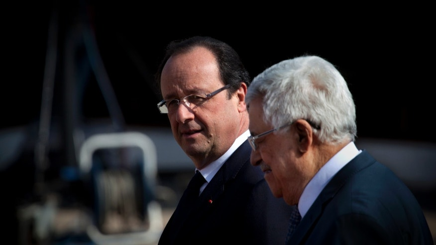 Palestinian President Mahmoud Abbas, right, walks French President Francois Hollande on his arrival to the Palestinian Authority headquarters, in the West Bank city of Ramallah, Monday, Nov. 18, 2013. (AP Photo/Nasser Nasser)