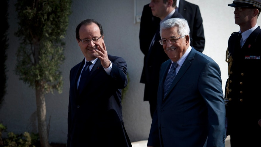 Palestinian President Mahmoud Abbas walks with French President Francois Hollande on his arrival at the Palestinian Authority headquarters, in the West Bank city of Ramallah, Monday, Nov. 18, 2013. (AP Photo/Nasser Nasser)