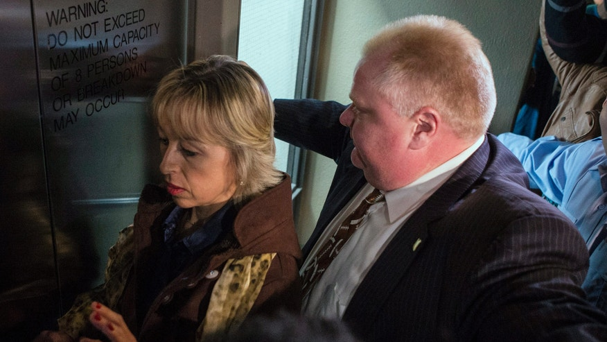 FILE - In this Nov. 14, 2013, file photo, Toronto Mayor Rob Ford stands at an elevator door as he tries to escort his wife, Renata, out of a news conference in Toronto. While the spotlight shines brightly on Toronto's embattled and erratic mayor, Rob Ford's wife and two children have remained almost invisible. (AP Photo/The Canadian Press, Chris Young, File)